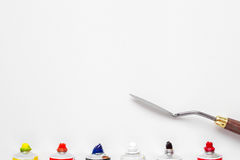 Palette knife and oil paint tubes on white canvas Royalty Free Stock Photo