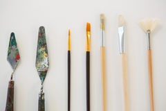 Palette knives and paint brushes arranged in a row Stock Photography