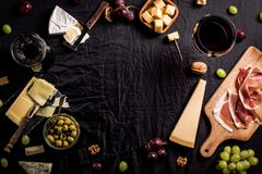 Some cheese and wine set. Palette of many types of cheese and some grapes, olives and wine with copy space royalty free stock image