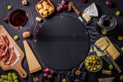 Some cheese and wine set. Palette of many types of cheese and some grapes, olives and wine with copy space royalty free stock photography
