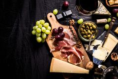 Some cheese and wine set. Palette of many types of cheese and some grapes, olives and wine with copy space stock photos
