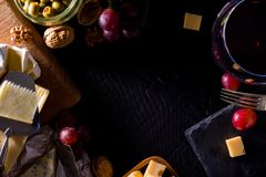 Palette of many types of cheese and some grapes, olives and wine. With copy space royalty free stock photography