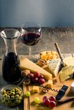 Palette of many types of cheese and some grapes, olives and wine.  stock photos