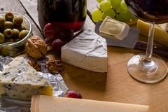 Palette of many types of cheese and some grapes, olives and wine.  royalty free stock photo