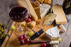 Palette of many types of cheese and some grapes, olives and wine.  royalty free stock image