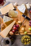 Some cheese and wine set. Palette of many types of cheese and some grapes, olives and wine stock photos