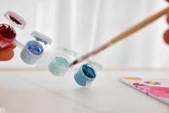 Palette mit Farben und Wasser mit einer Bürste für Kinder lizenzfreies stockfoto