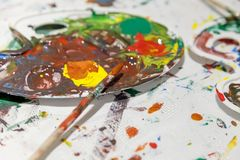 Palette with mixed colors with paintbrushes. Artistic concept, close up Royalty Free Stock Images