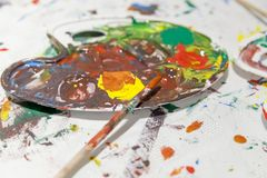 Palette with mixed colors with paintbrushes. Artistic concept, close up Stock Image