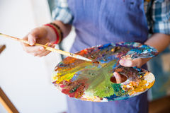 Palette with mixed paints holded by hands of woman artist Stock Photo