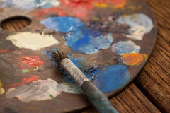 Palette with multiple colors and paint brush Royalty Free Stock Images