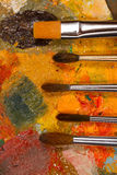 Palette with oil paint dried and  set of brushes. This palette mixed paints for hundreds of pictures. Painting for design studio , bar or restaurant Royalty Free Stock Images