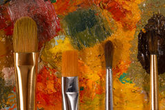 Palette with oil paint dried and  set of brushes Stock Photos