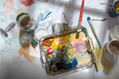 Palette and paint brush in artist hands stock photography