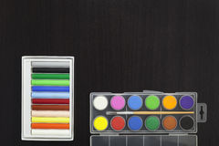 Palette with paint and brush,colorful chalk on dark black wooden. Table background Stock Photo