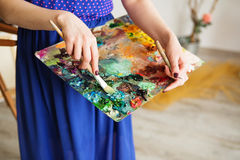 palette with paintbrush and palette-knife in artist's hands. Royalty Free Stock Image