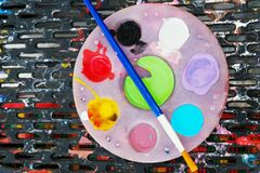 Palette with paints and brush. On plastic sieve background, Top view, Close up royalty free stock image