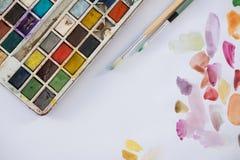 Palette, pinceaux et papier colorés Photographie stock