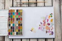 Palette, pinceaux et papier colorés sur la surface en bois Photographie stock