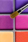 Palette of pink and purple eye shadow and the makeup brush, top view Stock Photos