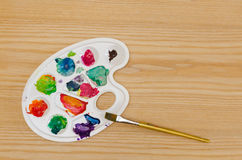 Palette with smudges of paint and a brush. On a wooden table Royalty Free Stock Image