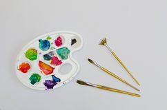 Palette with smudges of paint and painting brushes. Isolated palette with smudges of paint and painting brushes Stock Images