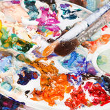 Palette with strokes of oils and two paintbrushes Royalty Free Stock Photo
