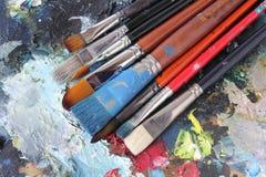 Palette und befleckte Pinsel Lizenzfreies Stockbild