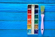 A palette of watercolor paint and a brush for painting on a blue wooden boards. Top view. Copy space. Art concept. A palette of watercolor paint and a brush for Royalty Free Stock Image