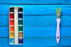 A palette of watercolor paint and a brush for painting on a blue wooden boards. Top view. Copy space. Art concept Stock Photos