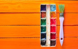 A palette of watercolor paint and a brush for painting on orange wooden boards. Top view. Copy space. Art concept. A palette of watercolor paint and a brush for Royalty Free Stock Photos