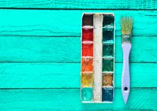 A palette of watercolor paint and a brush for painting on a turquoise wooden boards. Top view. Copy space. Art concept Stock Photos
