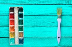 A palette of watercolor paint and a brush for painting on a turquoise wooden boards. Top view. Copy space. Art concept. A palette of watercolor paint and a Stock Photo