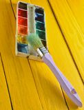 A palette of watercolor paint and a brush for painting on a yellow wooden boards. Art concept Stock Photography