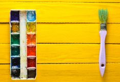 A palette of watercolor paint and a brush for painting on a yellow wooden boards. Top view. Copy space. Art concept Stock Image