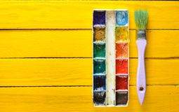 A palette of watercolor paint and a brush for painting on a yellow wooden boards. Top view. Copy space. Art concept stock images