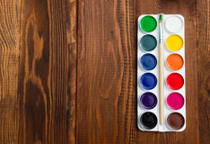 The palette of watercolor paints on a wooden background. Stock Photos