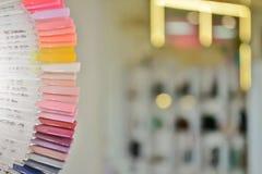 Paletten med färgprövkopior av stelnar polermedel från mörker till rosa färger, mot en bakgrund av oskarpa ljusa kulor och spegla royaltyfria bilder
