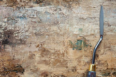 Palettenmesser auf Künstlersegeltuch mit Beschichtung der braunen Ölfarbe Stockfoto