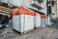 Paletter av vita kvarter eller askakvarter på konstruktionsplatsen av ny modern byggnad arkivfoton
