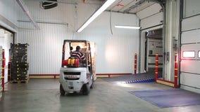 Paletter för laddarchaufförpåfyllning med askar av gods i släpet av lastbilen arkivfilmer