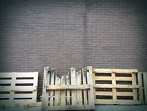 Paletter som lutar på tegelstenväggen Arkivbild