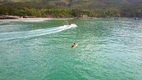 Palettes de surfer à bord des commandes de scooter de l'eau au delà banque de vidéos