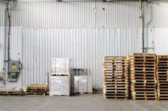 Palettes empilées à l'intérieur d'un entrepôt Photographie stock libre de droits