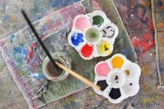 Palettes et pinceau sur la peinture de table Photographie stock libre de droits