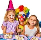 Palhaço da criança do aniversário que come o bolo com menino junto Miúdo com face desarrumado Imagens de Stock