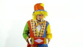 Palhaço de circo que sorri extensamente e que alcança para fora as mãos com a caixa brilhante nelas vídeos de arquivo