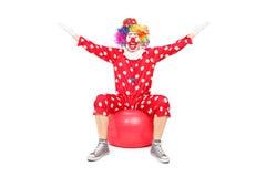Palhaço extático que senta-se em uma bola da aptidão Imagens de Stock Royalty Free