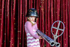 Palhaço fêmea novo no capacete que aponta o grande rifle Fotos de Stock