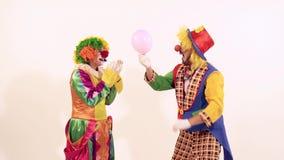 Palhaço masculino que infla um balão cor-de-rosa e que não dá ao palhaço fêmea filme